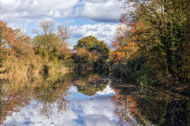Canal reflecting autumnal colours. royalty free stock photography