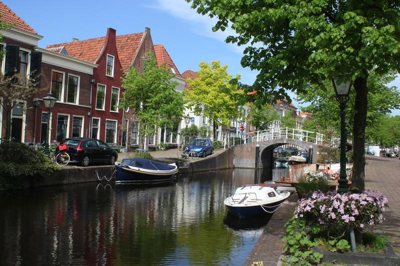 Canal in residential area of Leiden, Netherlands. Small boats, trees, bridge in typical canal scene in residential area of Leiden in the Netherlands on a sunny stock image