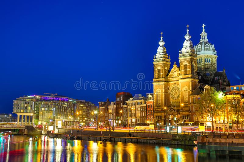Canal and St Nicholas Church in Amsterdam at twilight, Netherlands. Famous Amsterdam landmark near Central Station. royalty free stock image