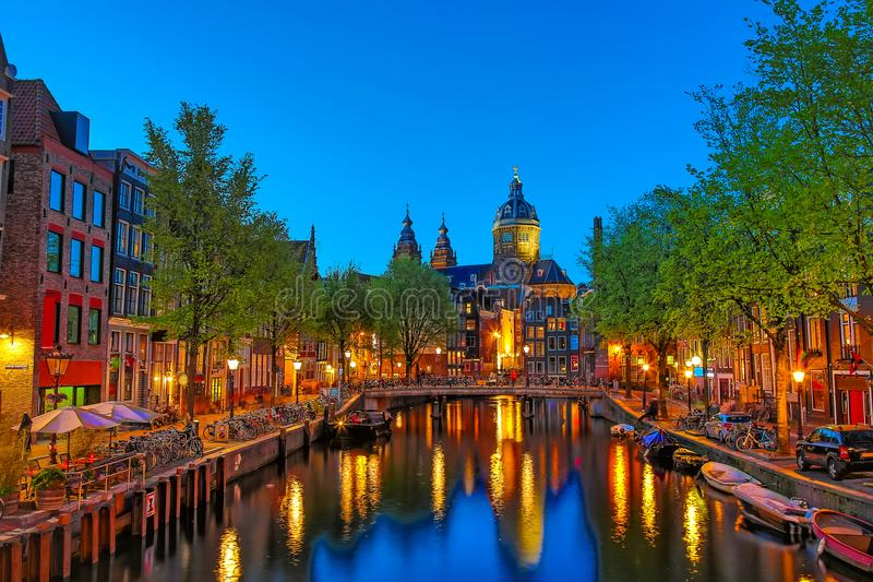 Canal and St Nicholas Church in Amsterdam at twilight, Netherlands. Famous Amsterdam landmark near Central Station. Canal and St Nicholas Church in Amsterdam at stock photography