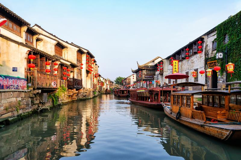 Canal in Suzhou, China. Suzhou, China - August 12, 2011: A canal in the middle of typical houses with paper lantern and wooden boats. Suzhou is often dubbed the royalty free stock image