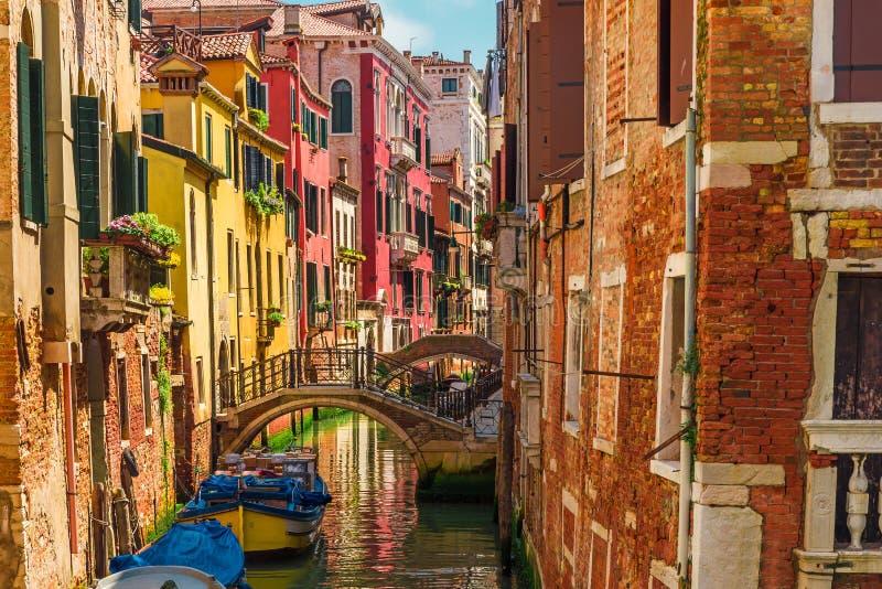 Canal Venetian com barcos e as fachadas coloridas de casas medievais velhas em Veneza, Itália foto de stock royalty free