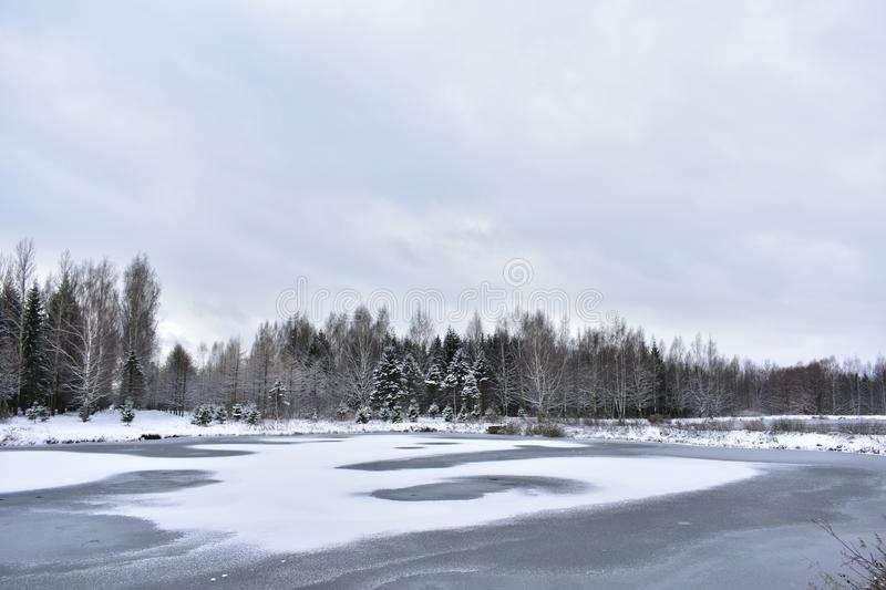 The canal was covered with ice and snow. Forest picturesquely painted tree branches frost snow and ice. Clouds stock photos