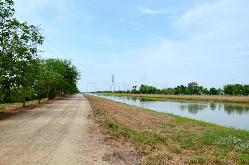 Canal watercourse waterway of water supply with water pipehigh v. Oltage pole in countryside Nonthaburi, Thailand royalty free stock photo