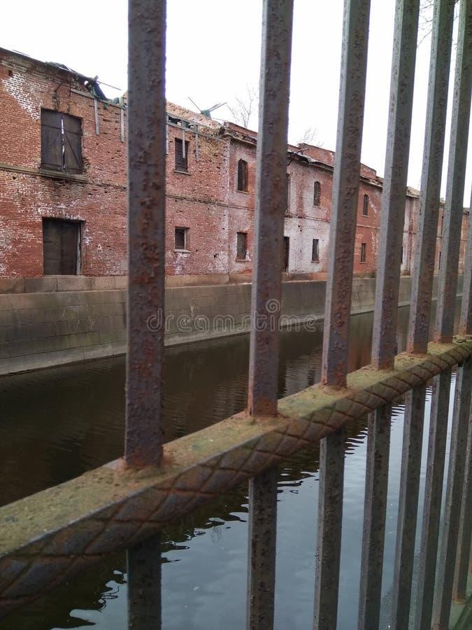 canal y edificio viejo detrás de la cerca imagenes de archivo