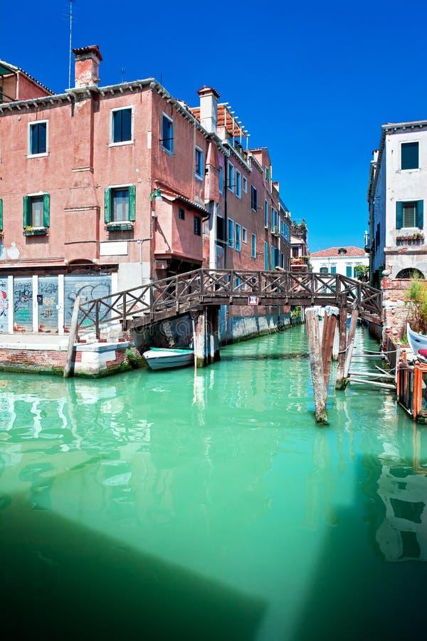 Canale colorato di Venezia con il ponte e case che stanno in acqua, I fotografie stock libere da diritti