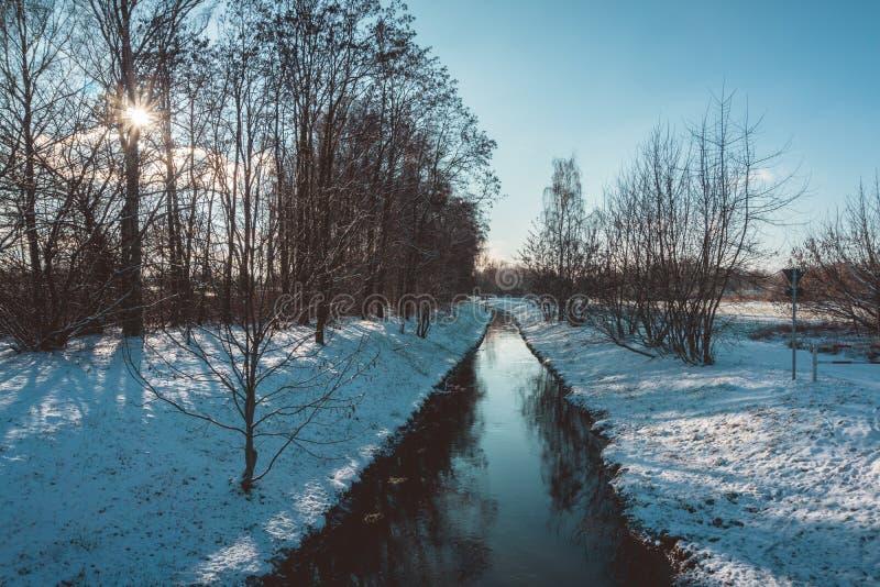 Canale tranquillo attraverso un paesaggio di inverno immagine stock