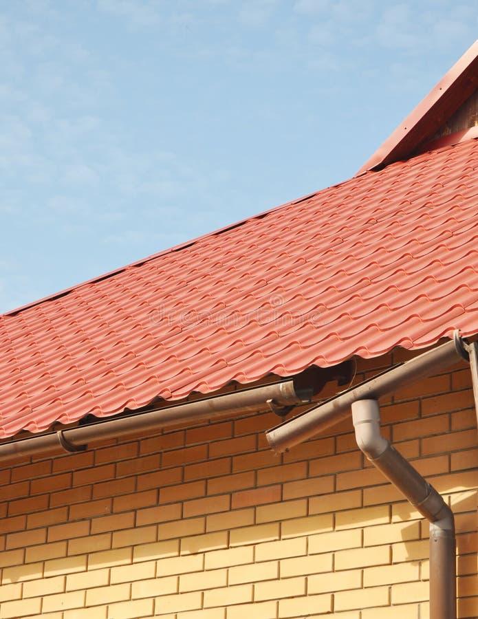 Canales quebrados de la lluvia con el tejado del metal Presa del hielo Primer en nuevo sistema roto del canal de la lluvia sin la fotos de archivo