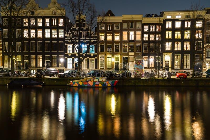 Canali a Amsterdam alla notte e ad una barca variopinta immagini stock libere da diritti