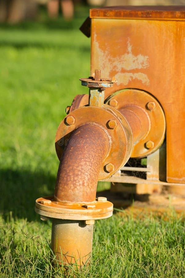 Canalisation rouillée de pompe d'approvisionnement sur l'herbe verte photos libres de droits