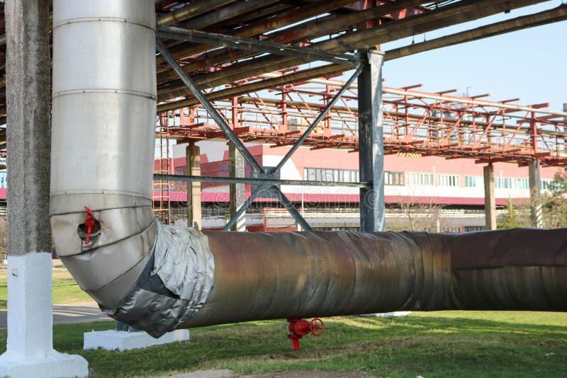 Canalize o estocada, grande tubulação com vapor na isolação feita das lãs de vidro com ventrals vermelhos, encaixes, válvulas, dr imagens de stock