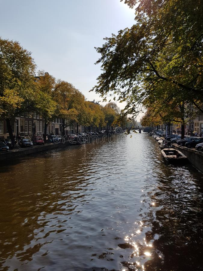 Canals of Amsterdam on an autumn day. Trees, water, river, skye stock image