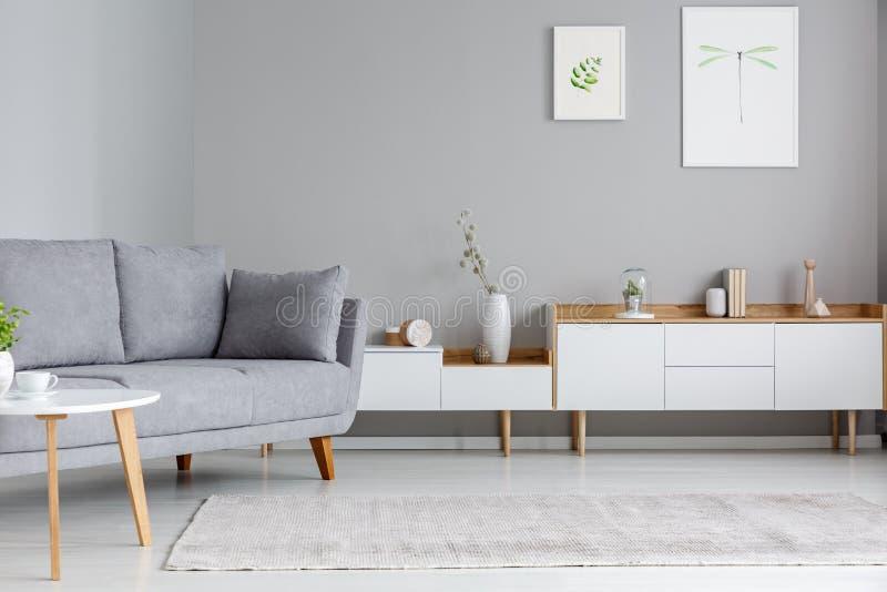 Canapé gris cerca del armario blanco en la sala de estar w interior del scandi foto de archivo