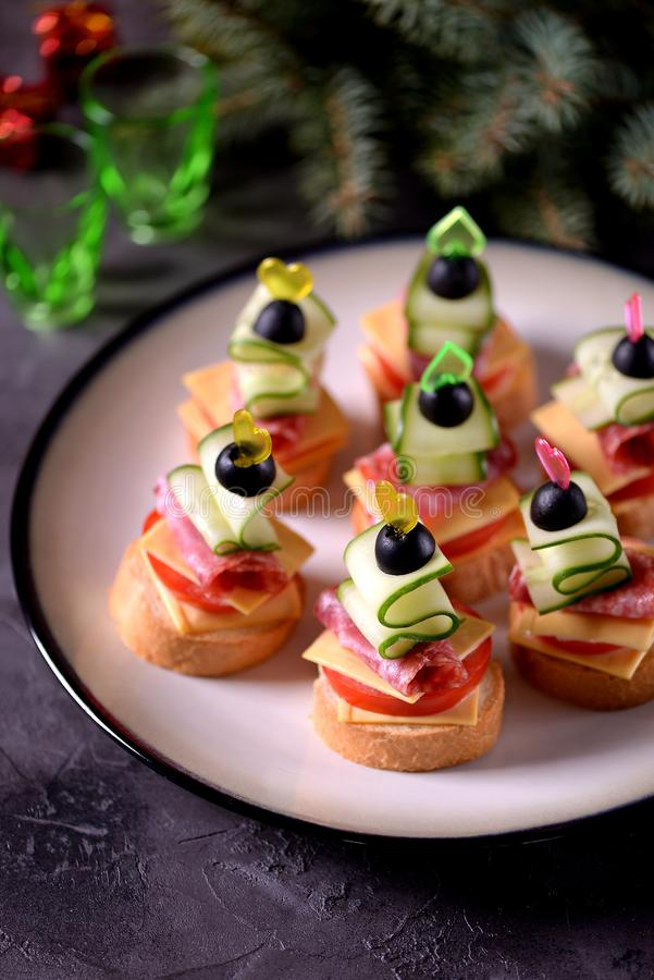 Canapé on skewer from bread baguette with toast cheese, sausage, tomato, cucumber and olives. Traditional snack for the New Year. royalty free stock photo