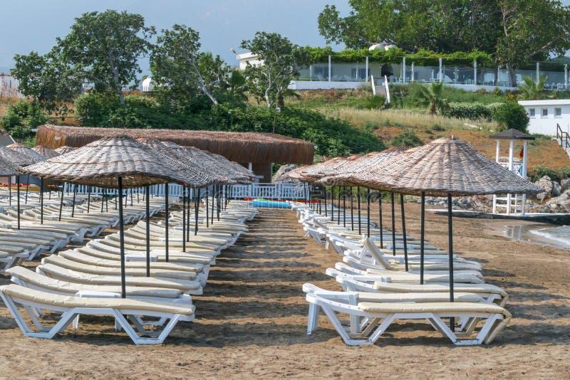 Canapés de Sun et parapluies en osier sur la plage locale de mer de la Chypre, fond de paysage marin photographie stock