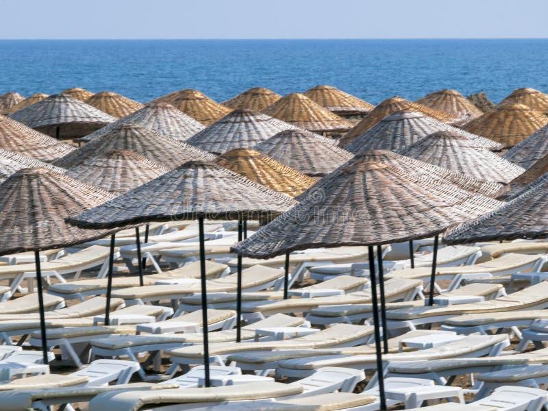 Canapés de Sun et parapluies en osier sur la plage de mer, fond de paysage marin photos libres de droits