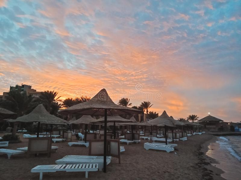 Canapés de Sun et parapluies de paille et beau coucher du soleil sur la plage de Hurghada, Egypte image libre de droits