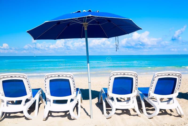 Canapés de Sun près de parapluie bleu sur la plage sablonneuse par la mer et le ciel Fond de vacances Horizontal idyllique de pla photo stock