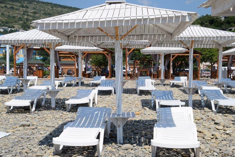 Canapés de Sun sous un auvent Infrastructure de la plage, protection contre le soleil image libre de droits