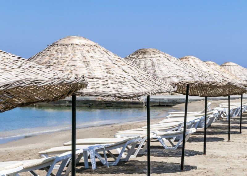 Canapés et parapluies de Sun sur la plage un matin ensoleillé d'été Fond avec la mer et le ciel bleus image libre de droits