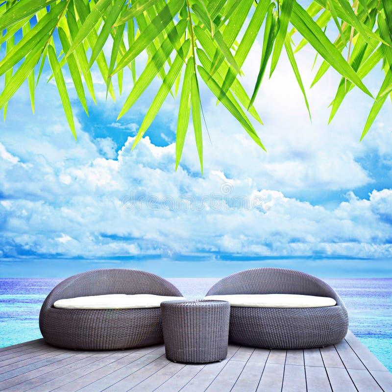 Canapés-lit en osier de détente tout près la mer photo stock
