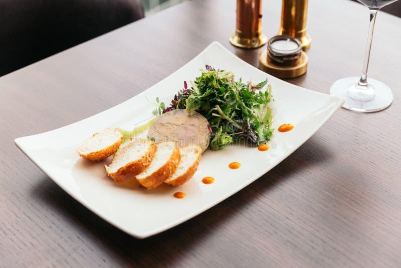 Canape avec des gras pâté et salade de foie servis avec du vin blanc photographie stock libre de droits