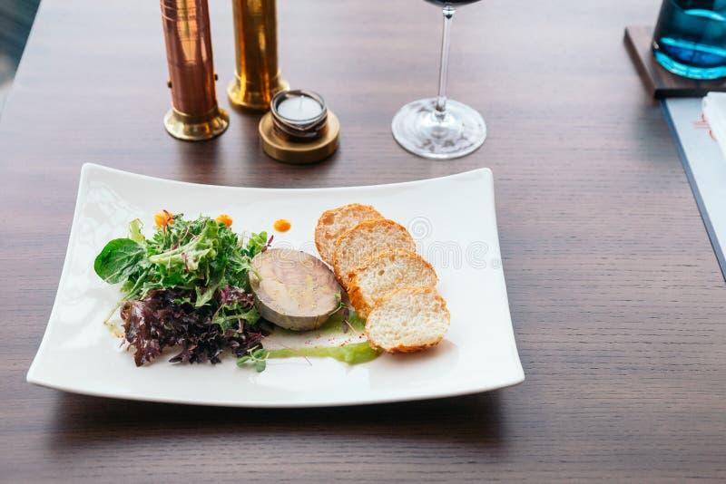 Canape avec des gras pâté et salade de foie servis avec du vin blanc photographie stock