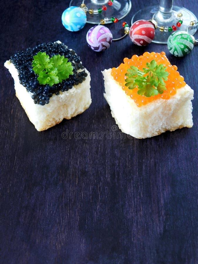Canape avec les verres rouges et noirs de caviar et de vin avec des décorations de Noël à l'arrière-plan image libre de droits