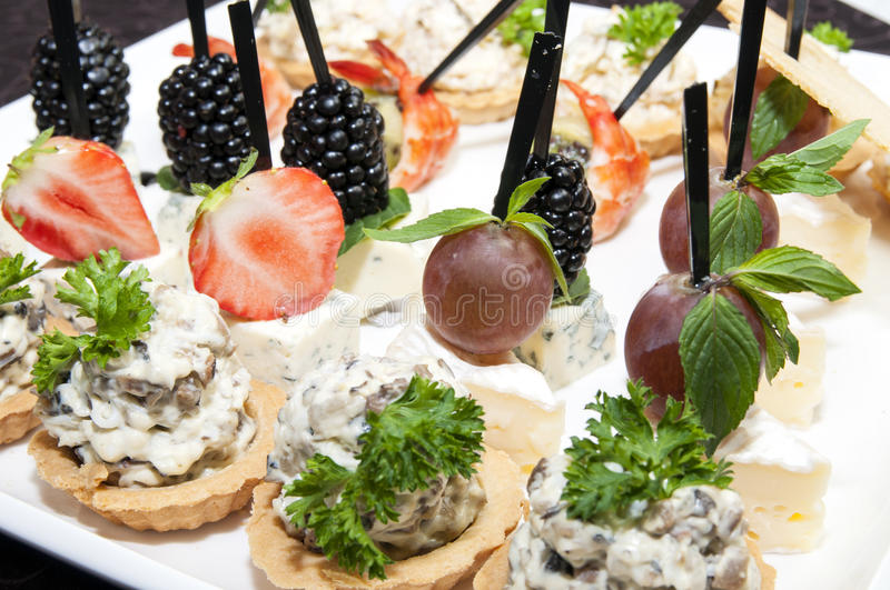 Canape. With cheese and berries on a plate in a restaurant stock images