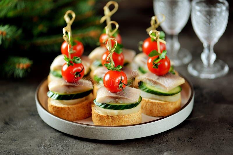 Canape com arenques salgados, pepino, as batatas fervidas e o tomate de cereja no pão torrado do centeio Fundo do Natal fotografia de stock royalty free