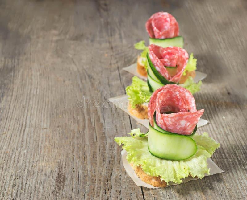 Canape com salame, pepino e salada na tabela de madeira fotografia de stock royalty free
