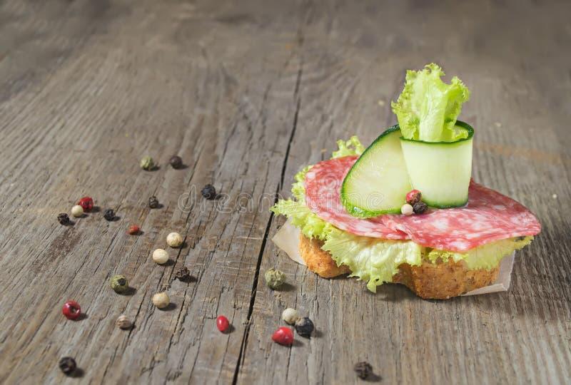 Canape com salame, pepino e salada na tabela de madeira imagens de stock