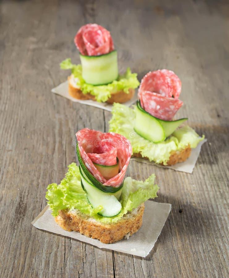 Canape com salame, pepino e salada na tabela de madeira fotos de stock