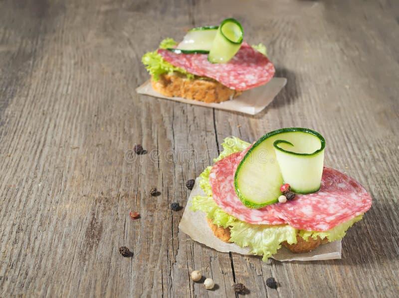 Canape com salame, pepino e salada na tabela de madeira foto de stock royalty free