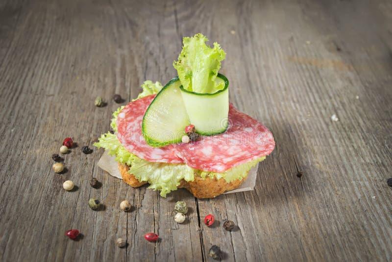 Canape com salame, pepino e salada na tabela de madeira fotos de stock royalty free