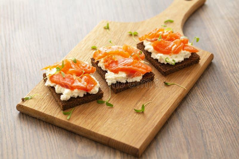 Canape com salm?o fumado e queijo creme na placa de madeira Foco seletivo imagem de stock royalty free