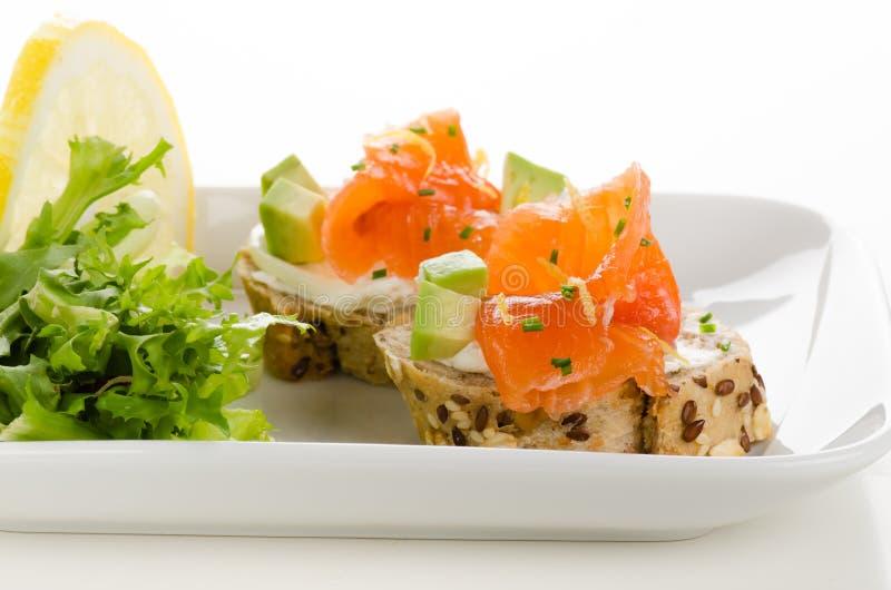 Canape con il formaggio cremoso, del salmone affumicato ed i cubi dell'avocado fotografia stock