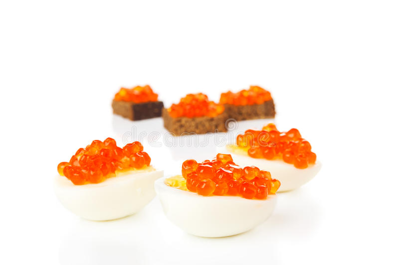 Canape con le uova ed il caviale rosso isolati su bianco immagini stock