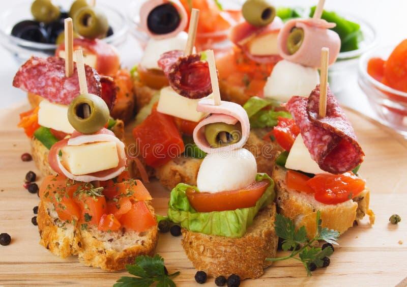 Canape con los ingredientes alimentarios italianos fotos de archivo