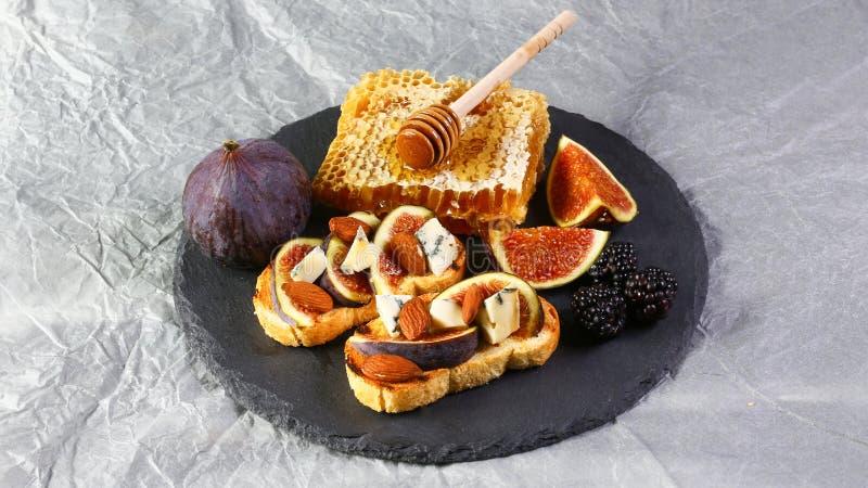 Canape of crostini met fig., schimmelkaas en prosciutto met honing en bessen op een schalie scheept in Vlak leg, kopieer ruimte royalty-vrije stock afbeeldingen