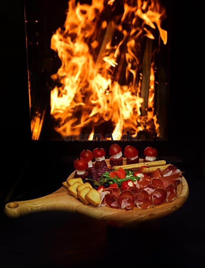 Canape of crostini met vleesbesnoeiingen op houten raad Heerlijk voorgerecht met canapeideaal als aperitief Het genoegen van stock fotografie
