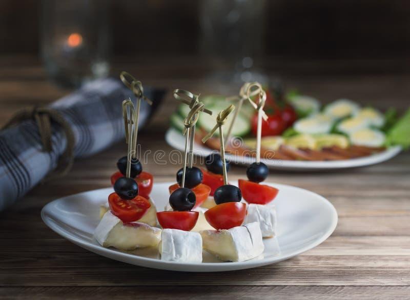 Canape del camembert de los tomates de cereza con las aceitunas y el jamón con las verduras y los huevos de codornices fotografía de archivo