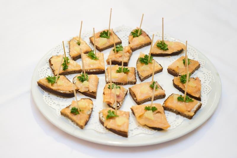 Canape del salmone affumicato su un piatto bianco sopra fondo bianco, Cl immagini stock