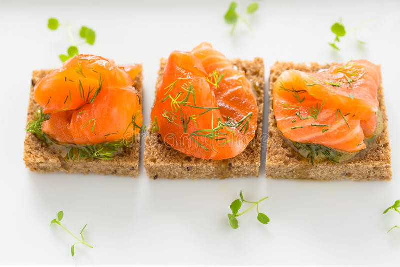 Canape deliziose dell'aperitivo di pane nero con il salmone affumicato immagine stock libera da diritti