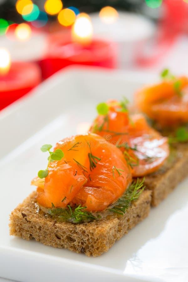 Canape deliziose dell'aperitivo di pane nero con il salmone affumicato fotografie stock