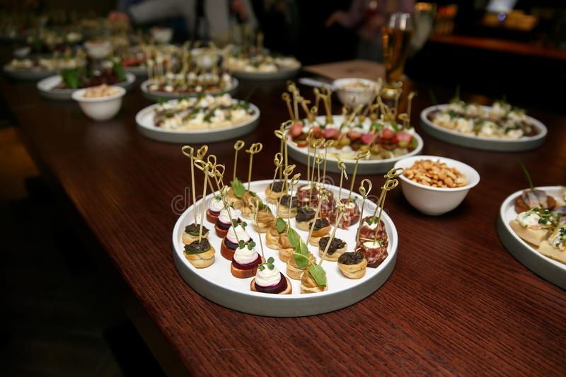 Different food snacks and appetizers in round plates on corporate event party. Celebration with catering banquet table. stock photos