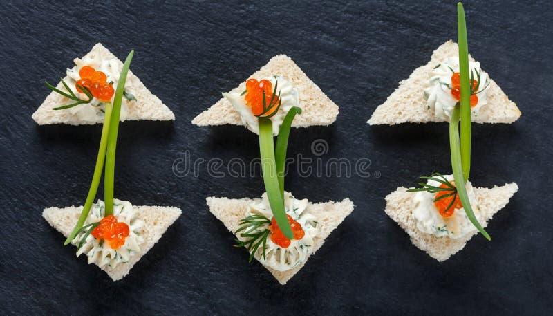 Canape do aperitivo com caviar e queijo creme vermelhos no fim de pedra do fundo da ardósia acima foto de stock