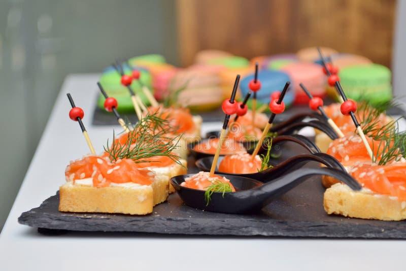 Canape do pão e dos peixes vermelhos, mentira em uma placa de pedra preta na tabela no fundo do banquete, o de madeira e o de vid fotografia de stock