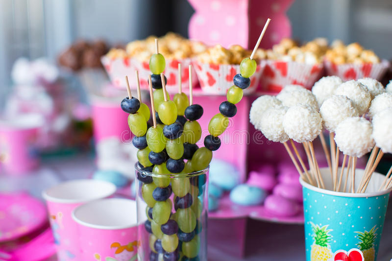 Canape of fruit, white chocolate cake pops and. Canape of fruit, white chocolate brownies and popcorn on sweet children's table at birthday party royalty free stock image