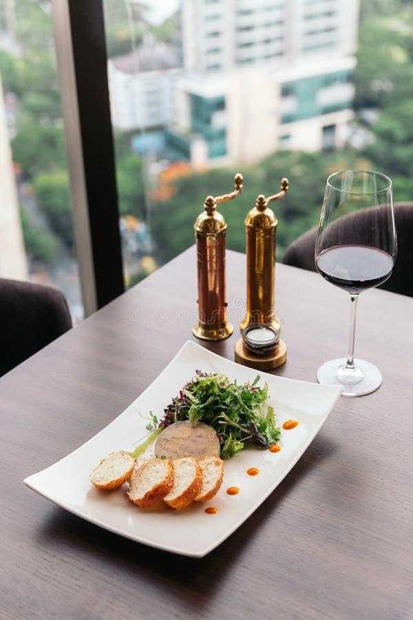 Canape med foiegras pate och sallad som tjänas som med vitt vin royaltyfri foto